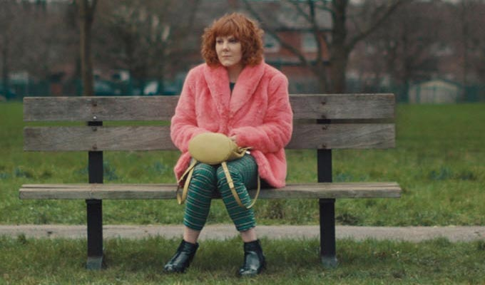 Sophie as Alma, sitting on a park bench in a vivid pink fur coat