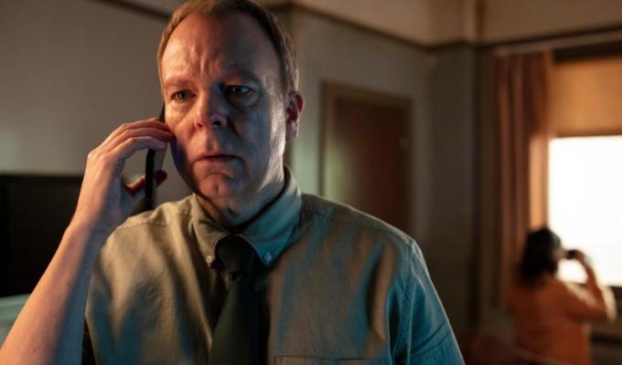 Pemberton on phone looking worried; Clifford behind him looking out of window with binoculars