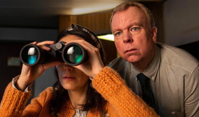 Sian looking through binoculars with Pemberton over her shoulder