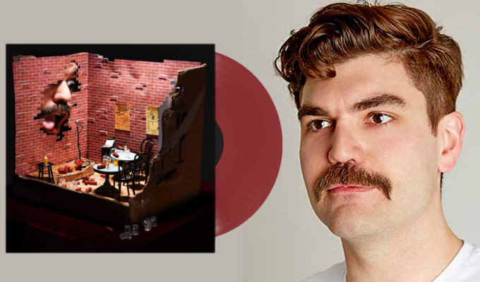 Album cover - big face poking through mini-comedy club wall
