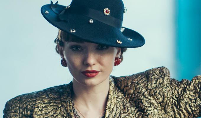 Tomlinson as Gaby in trendy designer hat