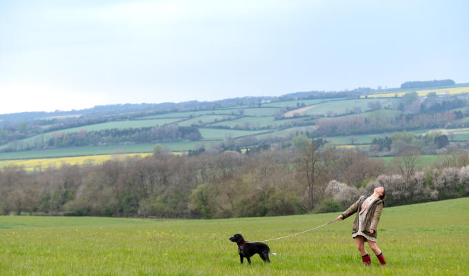 Picture shows Lucy, a tiny figure in a vast field, with a dog