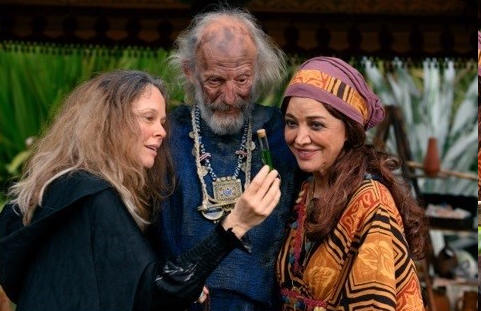 Old man with scraggly hair and dirty face with two women and a potion